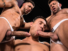 3 men stand in a black room, their white jockstraps barely containing their giant boners. FX Rios is tatted, pierced, and lean. Josh Conners is handsome, smooth, and muscled. Bruce Beckham is a unshaved bodybuilder with a macho attitude. After raw play wi