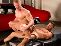 Huge muscled torsos of Johnny V and Landon Conrad compare to the muscle cars in the Auto Erotic Shop. And Johnny's smooth muscled chest contrast